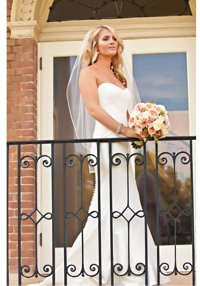 Bride in gown with bouquet on balcony