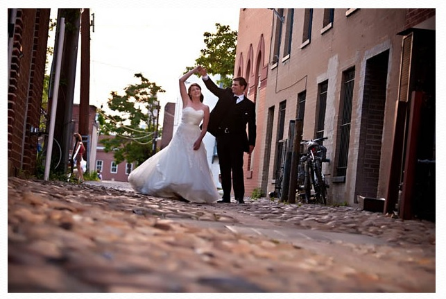 Bride and groom dancing in street.